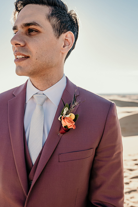 the groom in a rose pink suit with a white long tie