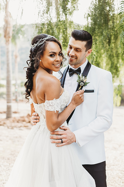 bridal hair with a braid and headpiece in a lace ballgown with an off the shoulder detail and the groom in a white with black shawl lapel tuxedo – bride walking down the aisle