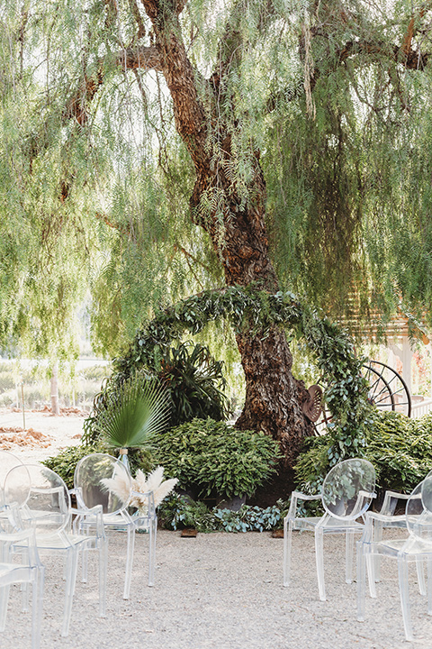 ceremony details with a green arch and acrylic chairs