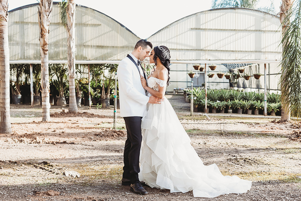 bride in a lace ballgown with off the shoulder neckline and groom in a white with a black shawl lapel tuxedo embracing outside the venue