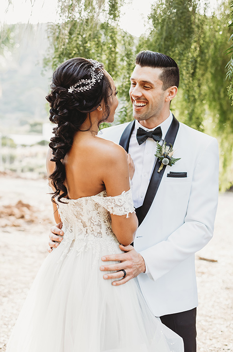 bride in a lace ballgown with off the shoulder neckline and groom in a white with a black shawl lapel tuxedo