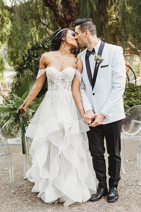 bride in a lace ballgown with off the shoulder neckline and groom in a white with a black shawl lapel tuxedo at ceremony