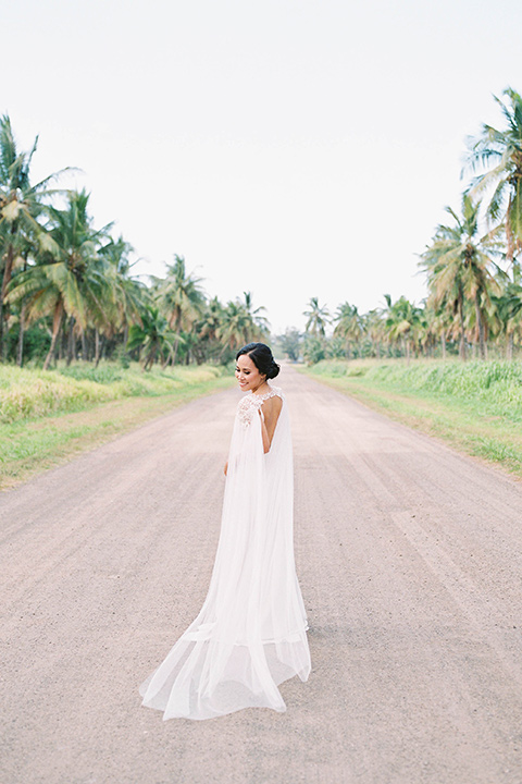 bride in a white formfitting gown with a long ethereal cape and her hair in a low bun