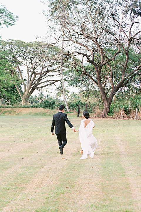 bride in a white formfitting gown with a long ethereal cape and her hair in a low bun and the groom in a black notch lapel tuxedo with bow tie outside pf venue