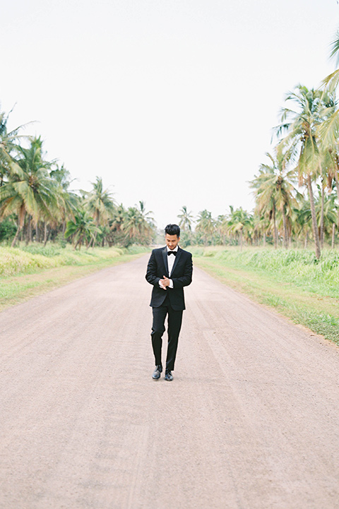 the groom in a black notch lapel tuxedo with bow tie