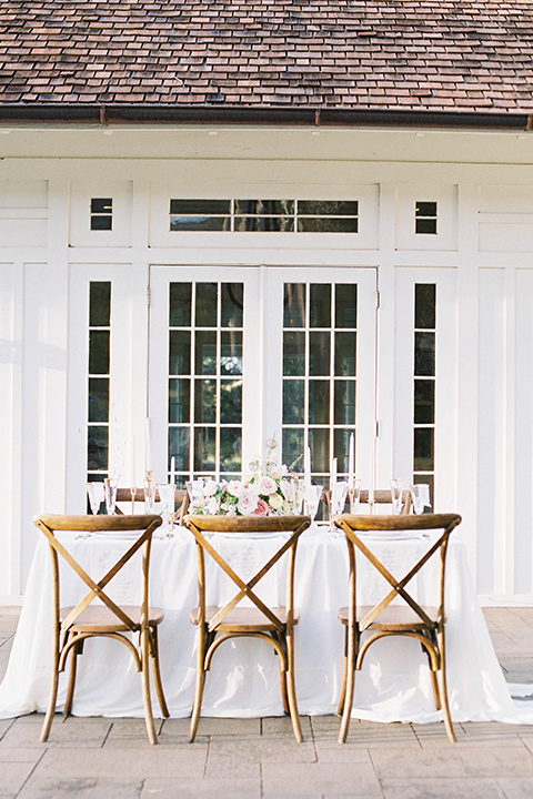 reception table set up with wooden farmhouse chairs and white table linens