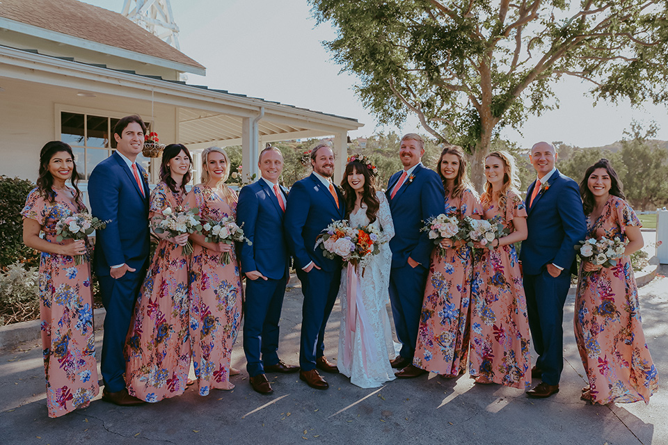 bride in a lace bohemian gown with tulip sleeves and a braided crown, the groom in a cobalt blue suit for purchase and the groomsmen in rental cobalt suits and the bridesmaids in pink floral gowns