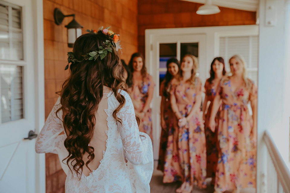 bride in a lace bohemian gown with tulip sleeves and a braided crown, and the bridesmaids in pink floral gowns