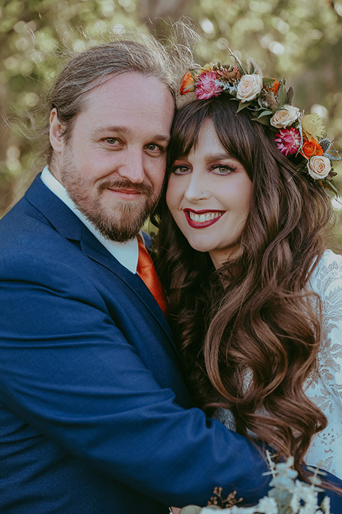 bride in a lace bohemian gown with tulip sleeves and a braided crown, the groom in a cobalt blue suit for purchase with a burnt orange tie