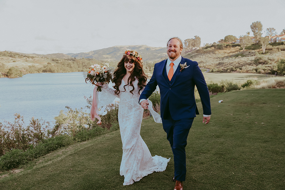 bride in a lace bohemian gown with tulip sleeves and a braided crown, the groom in a cobalt blue suit for purchase