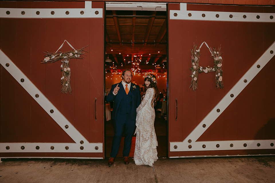 bride in a lace bohemian gown with tulip sleeves and a braided crown, the groom in a cobalt blue suit for purchase in front of a barn
