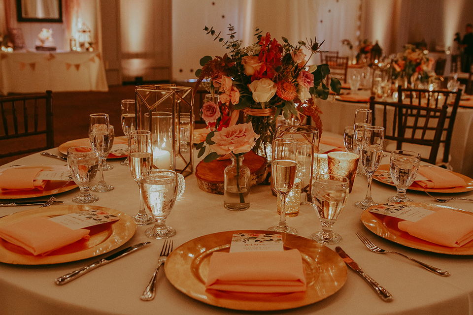 white table linens with burnt orange napkins and gold flatware