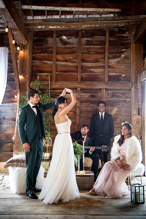 bride in a white ballgown with her hair in a loose brain and garden bouquet the groom in a green suit dancing with a live band