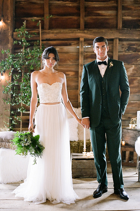 bride in a white two piece gown with a strapless neckline with her hair in a loose brain and garden bouquet the groom in a green suit walking in venue