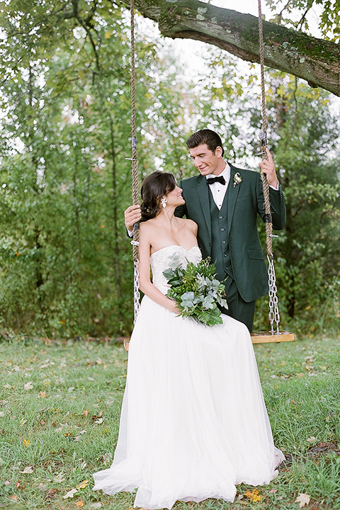 bride in a white ballgown with her hair in a loose brain and garden bouquet the groom in a green suit on the swing