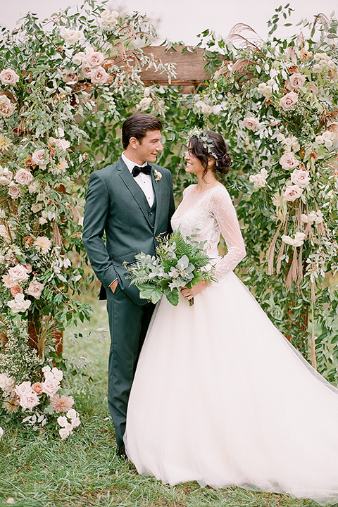 bride in a white ballgown with her hair in a loose brain and garden bouquet the groom in a green suit standing under the archway at the ceremony