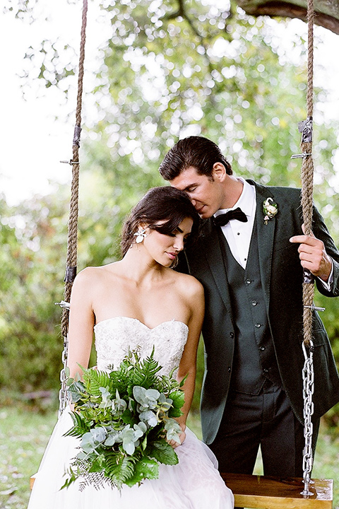 bride in a white ballgown with her hair in a loose brain and garden bouquet the groom in a green suit sitting on the swing together