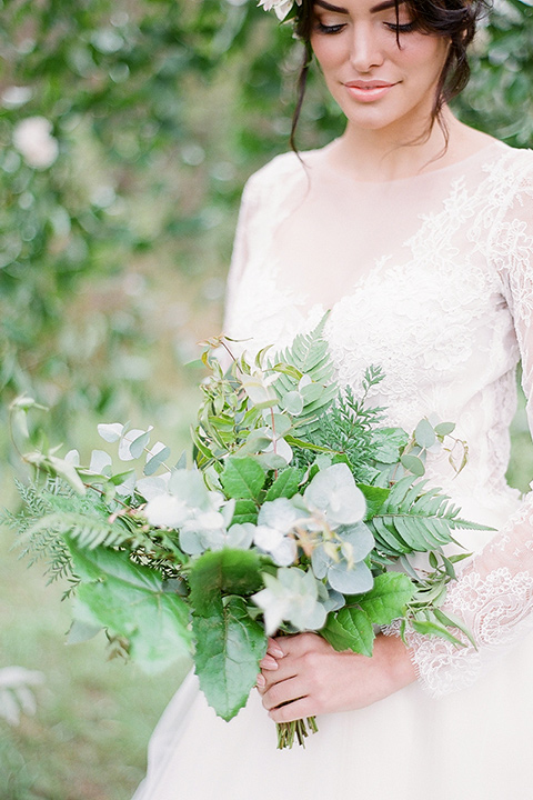 bride in a lace ballgown with long sleeves and a green and white bouquet