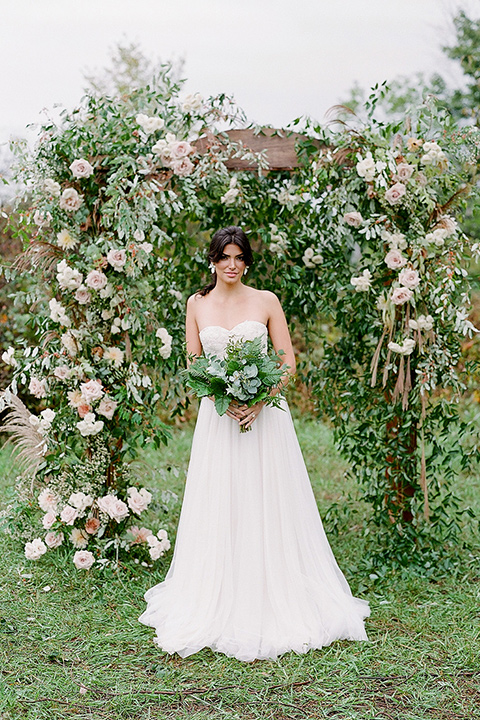 bride in a white ballgown with her hair in a loose brain and garden bouquet