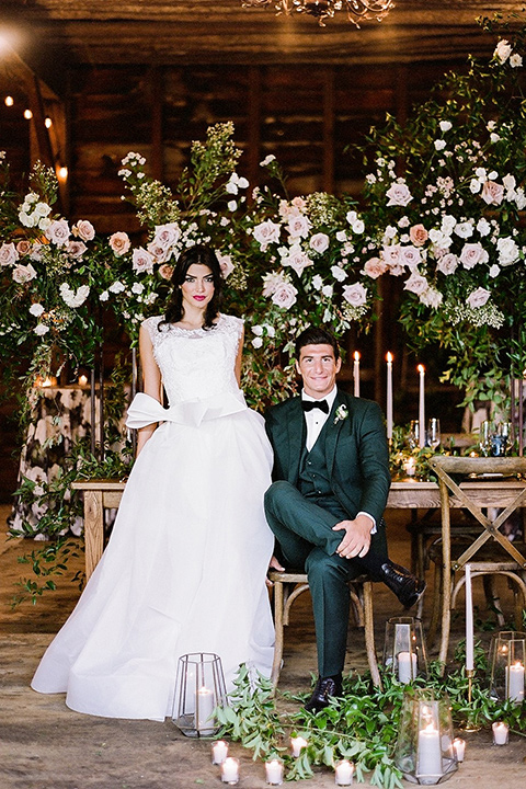 bride in a white ballgown with her hair in a loose brain and garden bouquet the groom in a green suit sitting