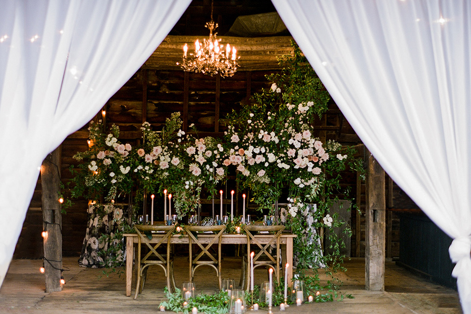 wooden table with green and rose flowers and white flowing linens