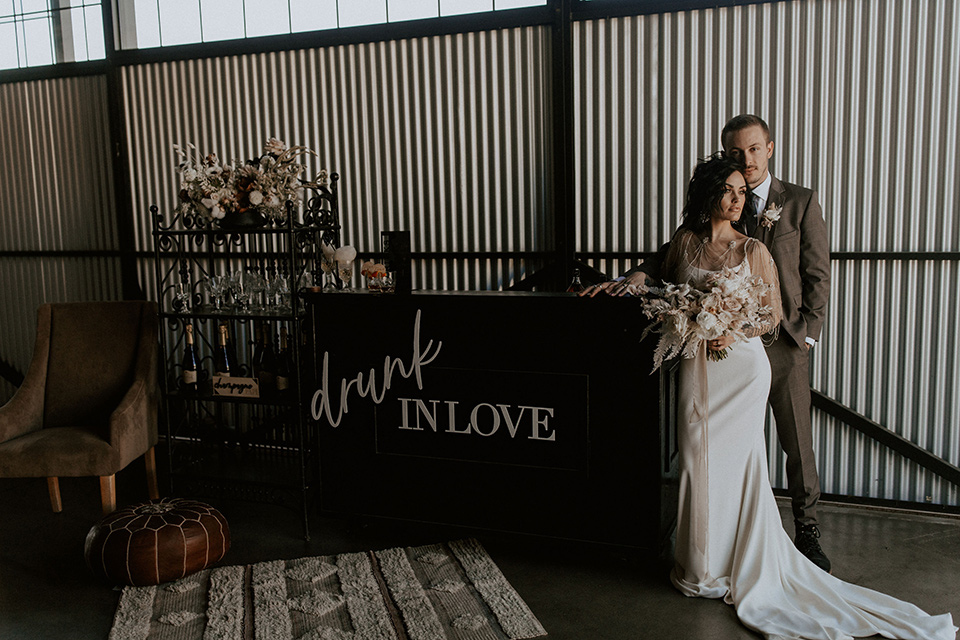 bride in a formfitting satin gown with a sheer cape and the groom in a café brown suit and chocolate long tie