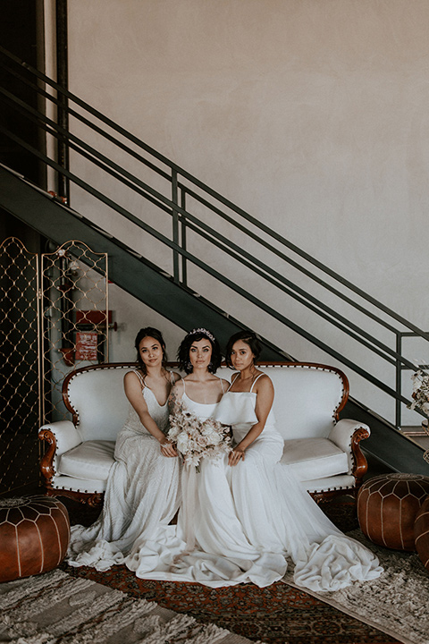 bride in a formfitting satin gown with a sheer cape and bridesmaids in white satin gowns