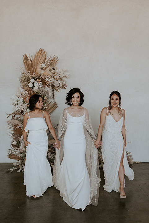 bride in a formfitting satin gown with a sheer cape and the bridesmaids in white satin gowns