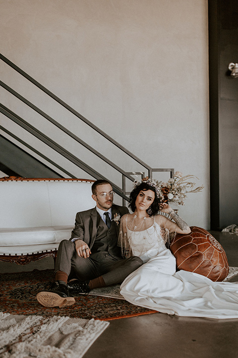 bride in a formfitting satin gown with a sheer cape and the groom in  café brown suit with a chocolate brown long tie