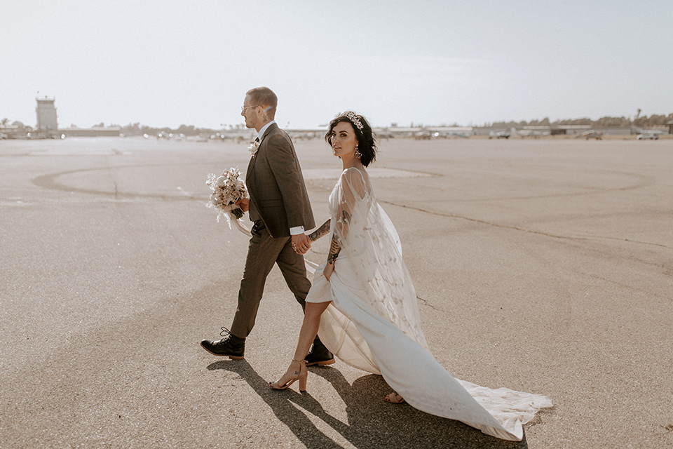 bride in a formfitting satin gown with a sheer cape and the groom in a café brown suit and chocolate long tie and the bridesmiads in white gowns