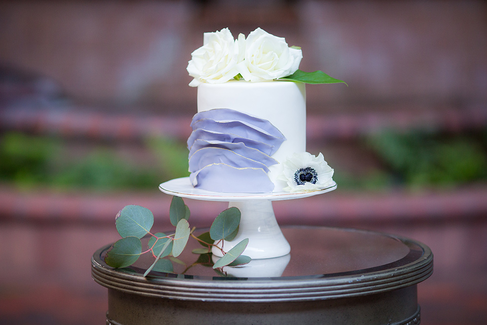 white and lilac colored cake with flowers on it