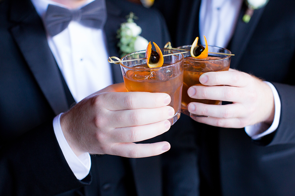grooms in black tuxedos with white shirts and black bow ties holding cocktails