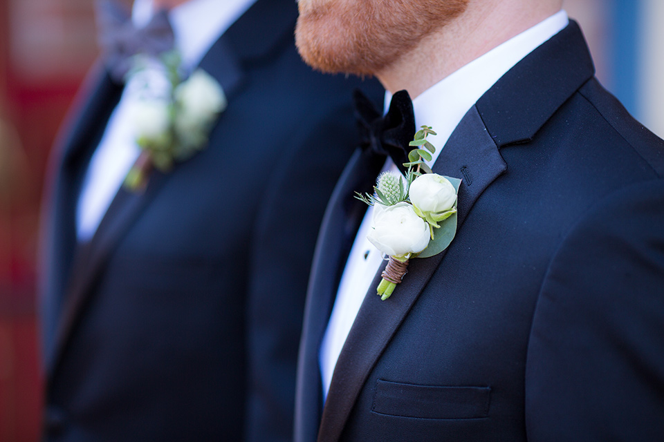 grooms in black tuxedos with white shirts and black bow ties