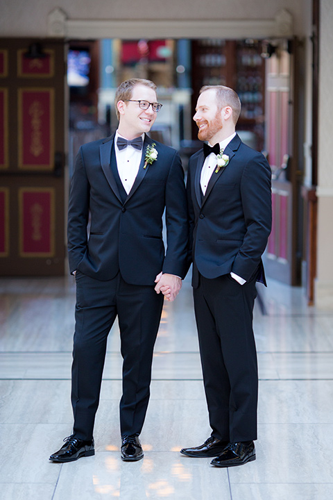 grooms in black tuxedos with white shirts and black bow ties standing outside
