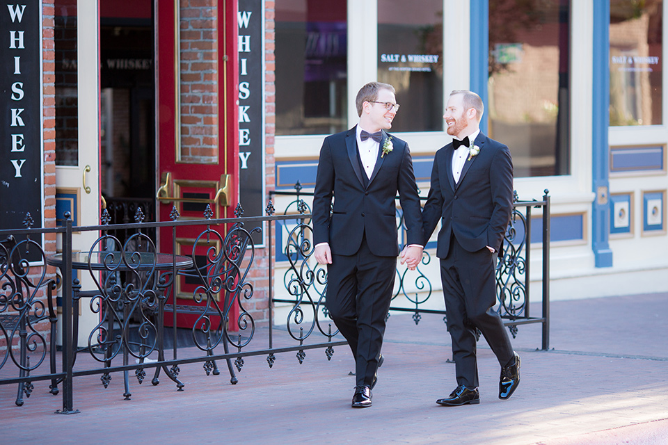 grooms in black tuxedos with white shirts and black bow ties walking outside venue
