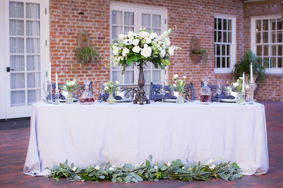 white table linens with tall white rose centerpieces