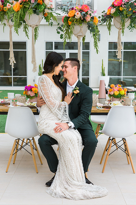 bride in a formfitting lace and crystal gown with bell sleeves and the groom in a dark green suit at the reception