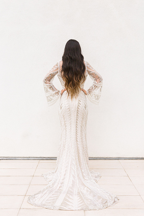 bride in a formfitting lace and crystal gown with bell sleeves