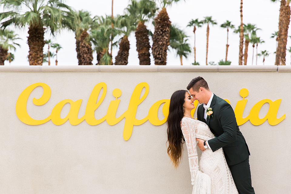 bride in a formfitting lace and crystal gown with bell sleeves and the groom in a dark green suit by California sign