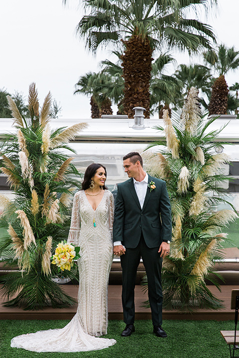 bride in a formfitting lace and crystal gown with bell sleeves and the groom in a dark green suit at the ceremony