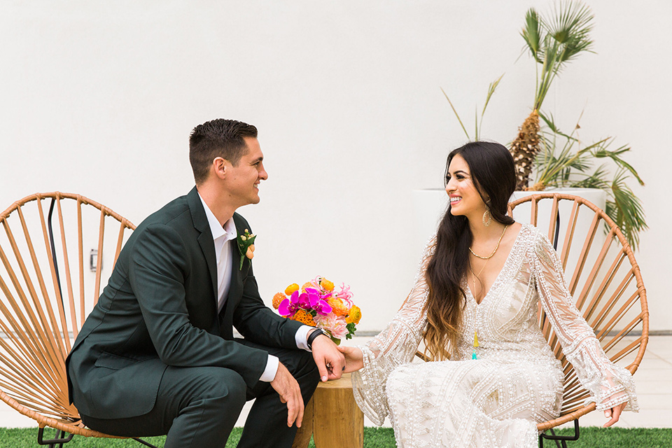 bride in a formfitting lace and crystal gown with bell sleeves and the groom in a dark green suit sitting in boho chairs