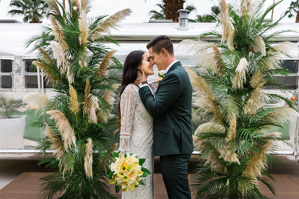 bride in a formfitting lace and crystal gown with bell sleeves and the groom in a dark green suit at ceremony