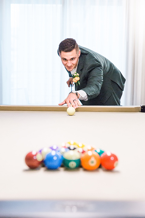 bride in a formfitting lace and crystal gown with bell sleeves and the groom in a dark green suit playing pool