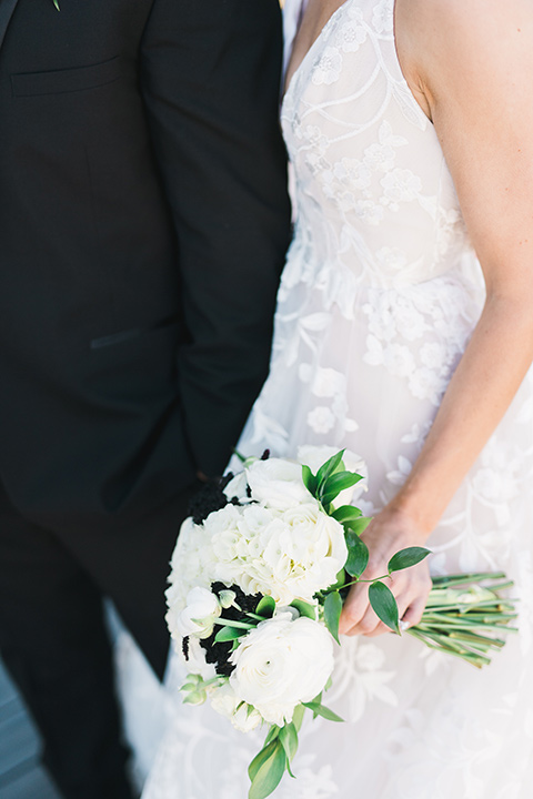 bride in a white gown with a deep v neckline and thin straps and the groom in a black tuxedo