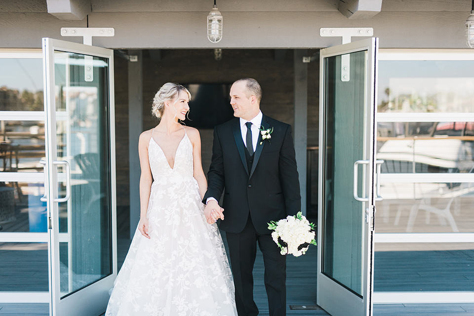bride in a white flowing gown with deep v neck line and thin straps, the groom is in a black tuxedo standing in the doorway of venue