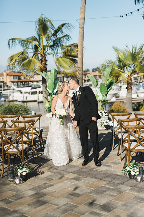 bride in a white gown with a deep v neckline and thin straps and the groom in a black tuxedo kissing at the ceremony