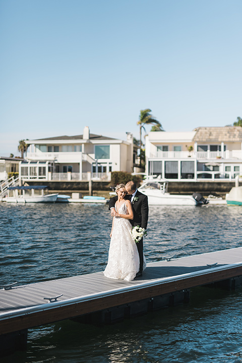bride in a white gown with a deep v neckline and thin straps and the groom in a black tuxedo on the dock