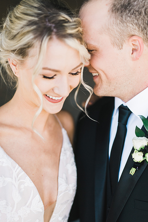 bride in a white flowing gown with thin straps and hair in a lose bun, the groom in a black tuxedo and black long tie close up together