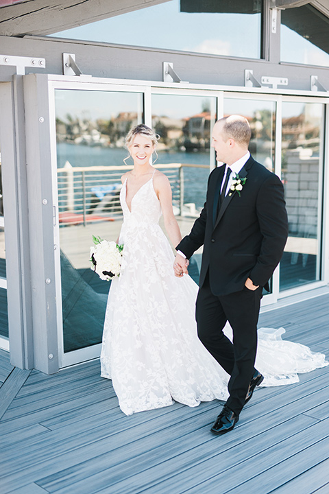 bride in a white flowing gown with thin straps and hair in a lose bun, the groom in a black tuxedo and black long tie- walking together
