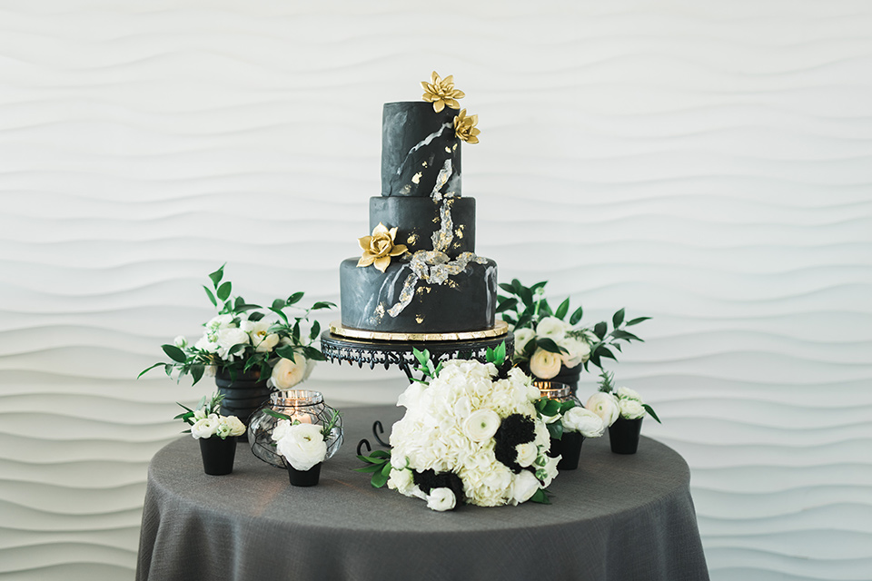 a cake with black fondant and silver and gold detailing